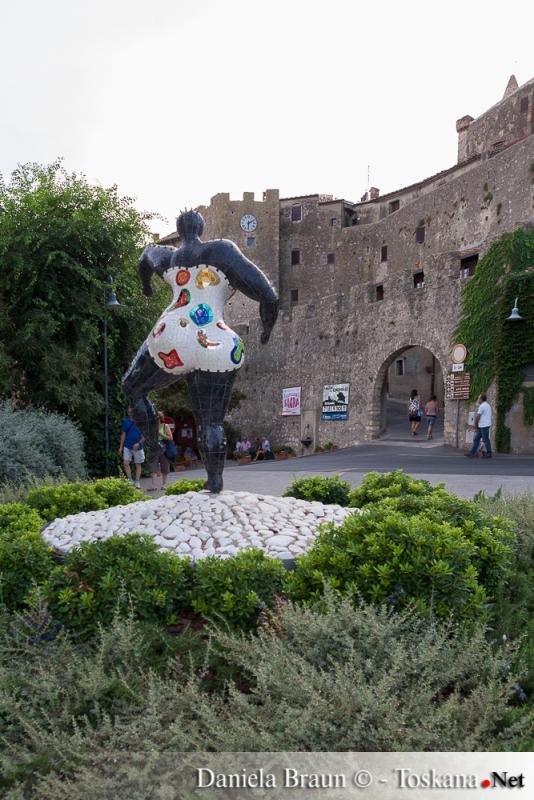Statue der Künstlerin Niki de Saint Phalle in Capalbio mit dem Stadttor im Hintergrund